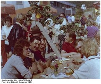 """September 1974, Orginal Bildunterschrift: """"Dedelow - Ein Dorf der sozialistischen Landwirtschaft der DDR. Ein Bier unter Männern. Nicht nur Frauen treffen sich gern zu einem Plausch, sondern auch die Männer. Sie kommen am Sonntag zum Frühschoppen vor der Gaststätte zusammen und werfen auch ab und zu einen Blick auf das schöne Geschlecht."""""""