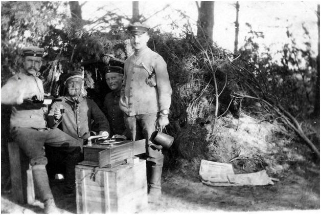 Galizien 1916, Oberarzt und Geschützbedienung vor ihrer Hütte bei Wein und Grammophonmusik.